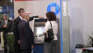 Attendees and exhibitors discuss bulk check deposits at Chase's booth.