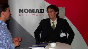 Ian Slater of Nomad Software hosts a guest in the company's booth.