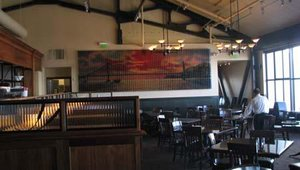 The upstairs décor of Bistro Boudin matches the architectural environment of the wharf and is attached to the Boudin Bakery museum. The windows to the left provide a view of the Golden Gate Bridge and the Pacific Ocean.