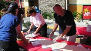 At the most recent opening in Oviedo, Fla., Lisa McClaren, Del Taco general manager (at left), and Barry Barnhart, vice president of franchise operations, help lay out 15 overlapping flour tortillas to create the 15-foot Macho Burrito.