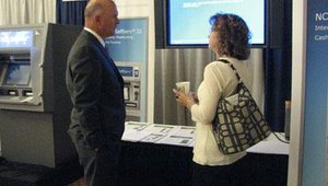 Ray Fendley, territory sales manager for NCR, speaks with an attendee about the Aptra Deposit Gateway, which ultimately is SaaS.