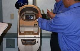 Tranax's VP of sales Bill Dunn and director of sales for self-service products Jeffrey Lee demonstrate the company's Mini-Bank 1500 ATM.
