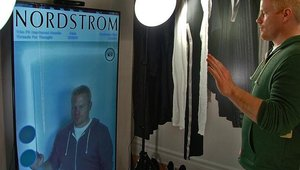 Samsung showed off a digital signage mirror that lets shoppers change the colors of the clothes they're trying on.