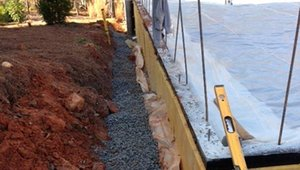 The yellow slab edge insulation and the black damp-proofing vapor barrier are used on both the stem wall and footing. A gravel covering drain tile next to the footing provides further protection against moisture.