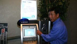 Tranax's director of sales for self-service products Jeffrey Lee demonstrates the Mini-Bank x4000 and biometrics check-cashing solution.