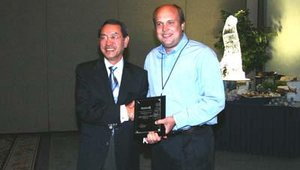 Tim Mathews from ATMequipment.com receives the second place award for Tranax dealer of the year. Dr. Hansup Kwon presented the award. This was the first year the company had a tie for second place.