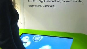 A passenger explores one of the multitouch tables that feature news and entertainment.