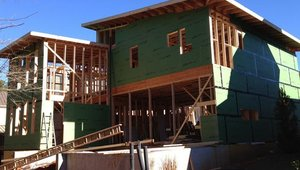 "The green board is Huber's R-Board Sheathing, an OSB coated with an air barrier and 1"" of insulation to reduce thermal bridging. The home also uses engineered lumber products for the roof and floor for  design advantages and reduced environmental impact."