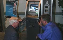 At right, John MacDougall, product manager for Retail ATM Products, and Phil Suitt, left, of ATM Ventures, review Tranax's Mini-Bank x4000, which uses Vero's biometrics check-cashing solution.