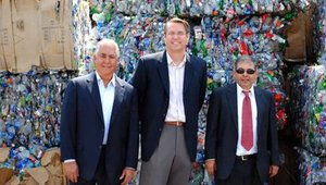 Rubio's Fresh Mexican Grill owner Ralph Rubio poses with Craig Snedden of Direct Pack Inc. and Nadim Bahou of Global PE in front of plastic bottles that will soon be recycled into packaging. Rubio's is using them for its salads.