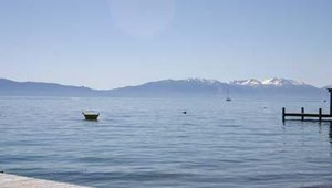 Snow-capped mountains can be seen in the background of Lake Tahoe's Meeks Bay.