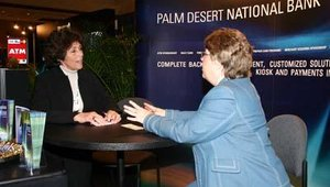 Gloria Grand, left, and Liz Nutting talk shop at the PDNB Electronic Banking Solutions booth.