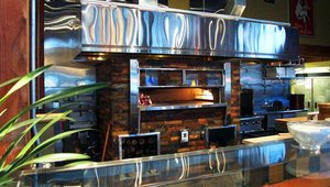 The stone hearth oven often serves as a visual centerpiece in a restaurant.