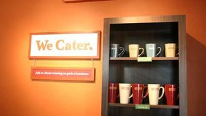 In addition to the bagel baking display, simple in-store signage touting Bruegger's services hang from the walls.