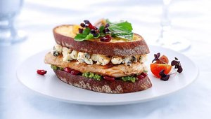 The Melthouse Bistro menu provides a description of each sandwich. The Dominique combines Wisconsin gorgonzola, parmesan, dried cranberries and grilled chicken breast smothered in walnut pesto on ciabatta bread.