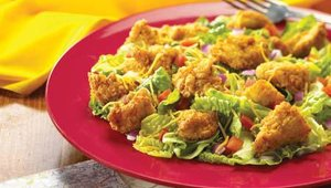 Rex's Chicken Salad features lightly breaded regular or jalapeno bite-side chicken on top of a crisp bed of iceberg and Romaine, with zesty cheddar cheese, red onion, fresh tomato and choice of dressing.
