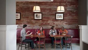 """The name Melthouse Bistro was created to convey """"comfort food,"""" """"passion for cheese"""" and """"approachable culinary."""" Walls covered in clean, white beadboard and distressed barn wood are alongside those painted in barn red and charcoal grey."""