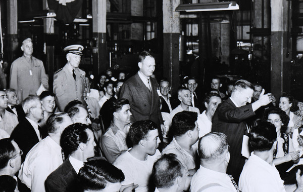 John Hazen White Sr. (center) is applauded by Taco Heaters employees at the awards ceremony on Aug. 10, 1945.