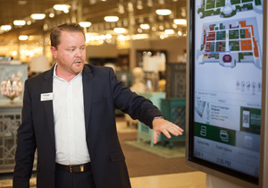Lee Summers, Manager of Marketing/Technology for Nebraska Furniture Mart, demonstrates a wayfinding display during an ICX Summit tour of the store.