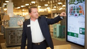 <p>A tour guide from Nebraska Furniture Mart shows off some of the in-store interactive customer experience tech to attendees.</p>