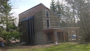 Over the 2-by-6 framing, the builder installed a continuous thermal blanket, draft protection, and water barrier consisting of plywood sheathing covered with a roller-applied elastomeric weatherproof coating, then mineral wool insulation board, then furring strips to create an air gap behind the metal and cedar siding.