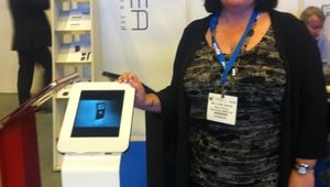 <p>Louise Janeway of Olea Kiosks poses with one of the firm's iPad enclosures.</p>
