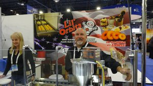 Brian O'gara serves fresh-baked donuts at the Lil Orbits booth, assisted by Bonnie Eveland.