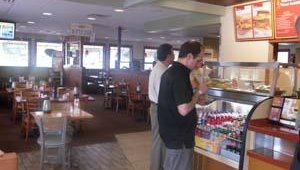 One-half of the dining area features seating for Fresh Express customers, the other half is seating for Denny's full-service customers. Jeff Epstein and Mark Peterson look over menu items while inside Denny's Fresh Express.