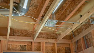 The well-sealed ducts are placed within the conditioned space between the floor joists to minimize energy loss while spray foam insulates and air-seals the rim joists.