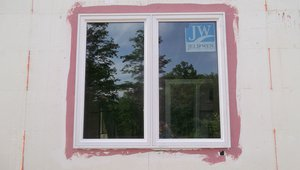 The high-performance window system includes very efficient windows and a comprehensive paint-on flashing that contributes to a continuous wall water barrier.