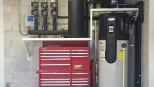 An ultra-efficient geothermal heat pump heats and cools the home and preheats water for the heat pump water heater.