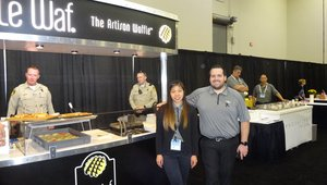 Ana Mae Simpson and Paul Landauro present artisan waffles at the le Waf exhibit in the Sysco pavilion.