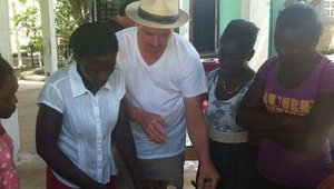 Smoke Restaurant chef Tim Byres teaches women in Jacmel's Organisation Tendre Enfance how to safely carve and prepare a chicken.