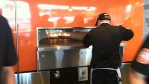 <p>The pizzas are fired in a Wood Stone oven and customers can watch their pizzas being cooked in about 3 minutes before they're delivered to in-store customers.</p>