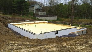 Closed-cell spray-foam insulation forms a continuous thermal blanket beneath the foundation slab.
