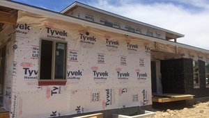 Taped house wrap provides an air and water barrier over OSB sheathing on the 2-by-6 advance-framed walls, which are dense packed with blown fiberglass and air-sealed with a sprayer-applied sealant.
