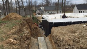The basement walls are made of ICF blocks that provide continuous layers of insulation along the interior and exterior of the foundation walls, while dimpled plastic mats shed water away from the structure.