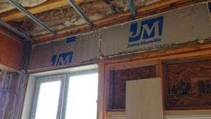 Rigid foam is sealed into place with canned spray foam to insulate and air-seal the header spaces above the windows.