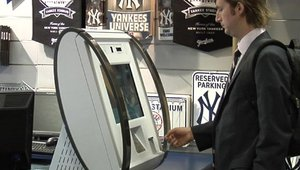 A customer tries out the new KAL cashless RTM. The compact terminal dispenses vouchers that can be redeemed for cash at the POS. The system automatically credits the merchant's bank account with the amount of the customer's cash transaction.