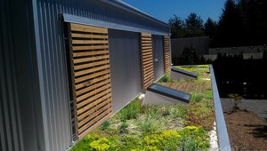 "Sliding wooden screens provide shading on south-facing windows, while the planted ""green"" roof helps control storm water runoff."
