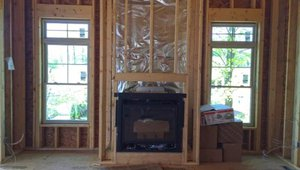 The foil-faced insulation behind this fireplace provides an air barrier and thermal shield.