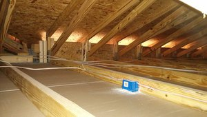 The attic has raised heel trusses to allow for full insulation depth at the eaves. Vertical insulation dams were installed in each rafter bay to keep insulation in and wind out of the vented attic.