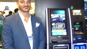 Jason Ferreira presents a ticket redemption and bill breaking kiosk at the NRT booth during the Global Gaming Expo in Las Vegas.