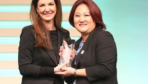 Kat Cole, Cinnabon CEO, hands Julie Lim, of Royal Cup Coffee, an award for Volunteer of the Year.