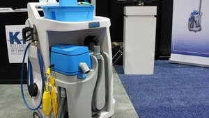 The Ecolab Cleaning Caddy is a touch-free restroom cleaning caddy with lock-and-key chemical dispensing, spray wand, on-board wet vac, and rechargeable battery in a footprint the size of a mop and bucket.