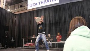 A member of the award-winning World Pizza Champions spins the dough.