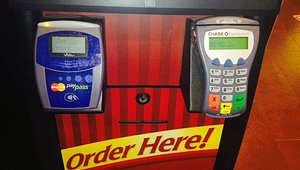 Tim Hortons customers can pay by sliding their debit card (in the terminal on the right) or by tapping their NFC-enabled smartphone on an NFC-enabled terminal (left).