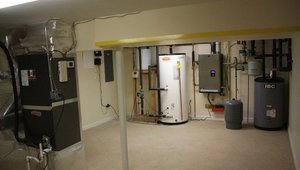 <p>The mechanical room in the basement houses the water heating equipment, including the storage tank and wall-hung boiler as well as the air handlers for the hydro coil and the high efficiency (16 SEER) air conditioner.</p>