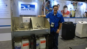 Harrison Maichle presents a portable sink at the Ozark River Portable Sinks booth.