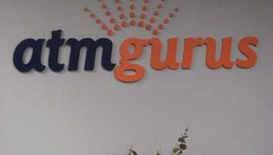 The ATMGurus logo is prominently displayed throughout the facility.